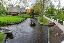 Man Steering A Boat Through The Canals Of Giethoorn Village Also Known As Dutch Venice