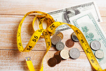 Measuring Tape, Coins And Dollar Bills On The Table