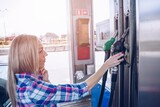Woman holding a fuel nozzle. Bauty woman is going to refuel the car.