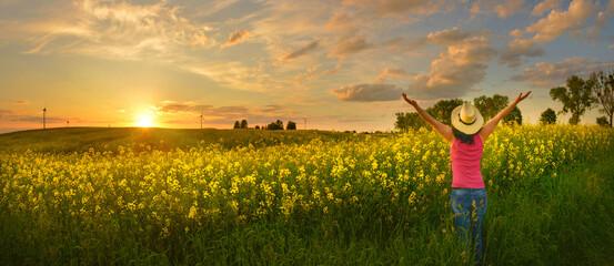 Happy woman enjoys beautiful sunset on flower field