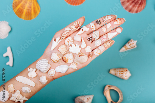 Fotografía Closeup of hand holding different kinds of seashells, corals ans surrounded by conches in front of a blue background, isolated with a caption for text