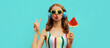 Summer fashion portrait of young woman in headphones listening to music with juicy slice of watermelon, female model blowing her lips posing on a colorful blue background