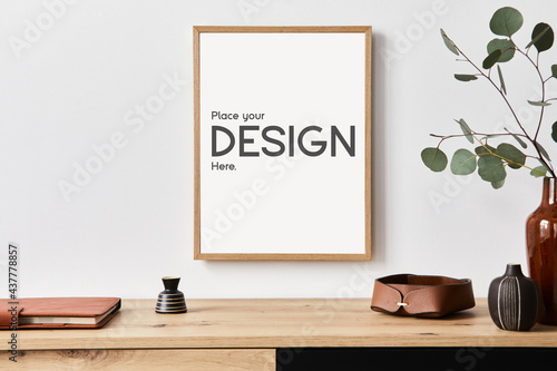 Stylish interior of living room with mock up poster frame, wooden commode, book, eucalyptus leaf in ceramic vase and elegant personal accessories. Minimalist concept of home decor. Template.