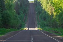 A Flat Asphalt Road With New Markings Runs Through Very Hilly Terrain