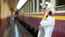 Side View Of Young Beautiful Female With Hat And Sunglasses Smiling While Waiting For The Train