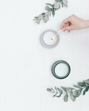 Womans Hand Uses Match To Light Aromatic Candle In Glass Jar On White Wooden Table With Eucalyptus Branches.