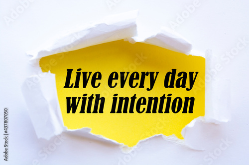 Live every day with intention. Words written under torn paper. Motivation concept text.