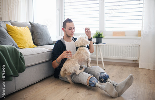 Fotografiet Portrait of disabled young man playing with dog indoors at home, leg prosthetic concept