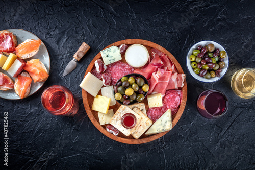Charcuterie and cheese board, overhead flat lay shot with copy space on a black background. Italian antipasti, shot from above with wine, olives, and sanwiches. Mediterranean delicatessen