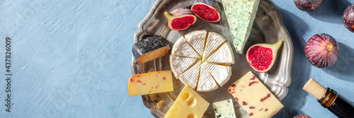 Cheese, fruit, and wine panoramic header with a place for text, overhead flat lay shot on a blue background. Camembert, blue cheese, etc