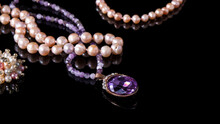 Sparkling Purple Old Amethyst Pendant, Amethyst Beads, And Iridescent Pearl Necklaces On A Black Background. Luxurious Isolated Natural Jewelry.
