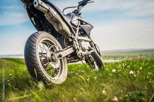 Fotografiet The motorcycle stands on a hill overlooking a beautiful landscape with green meadows