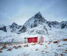 Winter Landscape In North Norway: Red Barn Against Snow Covered Mountains