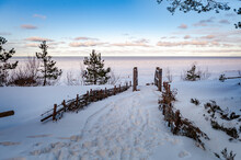 Footbridge Over A Dune At The Beach In Latvia. Baltic Sea. Wooden Steps Leading To The Frozen Sea. Snowy Winter Landscape