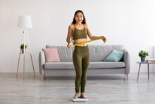 Full Length Portrait Of Slim Indian Woman Measuring Her Waist While Standing On Scales At Home, Full Length