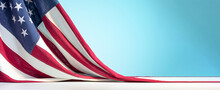 United States Of America Flag On White Table On Blue Sky Background. Celebration Of The Fourth Of July Or US Independence Day Backdrop