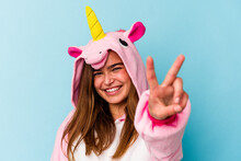 Young Caucasian Woman Wearing An Unicorn Pajama Having Fun Isolated On Blue Background