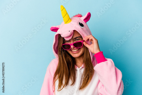 Foto Young woman wearing an unicorn costume with sunglasses isolated