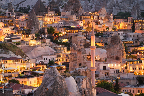 Goreme, Cappadocia, Turkey. View of the evening city from the mountain. Bright evening city. Landscape in the summertime. UNESCO heritage. Vacation and tourism. #437884414