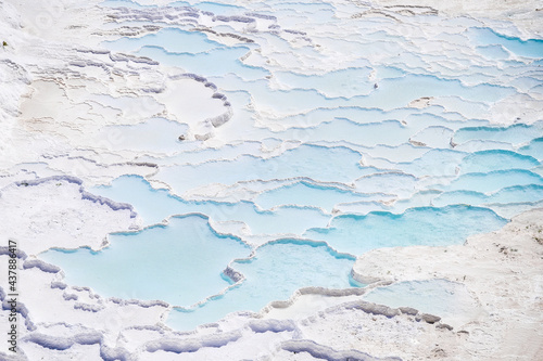 A view of the travertines. Pamukale, Turkey. Blue water in the terraces. A popular place for tourism. White rocks and water. #437886417