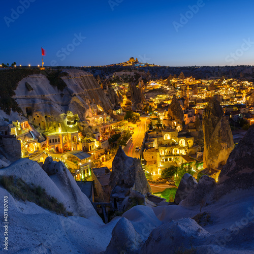 Goreme, Cappadocia, Turkey. View of the evening city from the mountain. Bright evening city and clear sky. Landscape in the summertime. UNESCO heritage. Vacation and tourism. #437887078