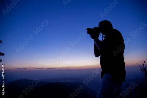 Fototapeta photographer on the top of mountain at sunset