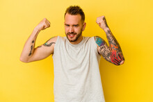 Young Tattooed Caucasian Man Isolated On Yellow Background Showing Strength Gesture With Arms, Symbol Of Feminine Power