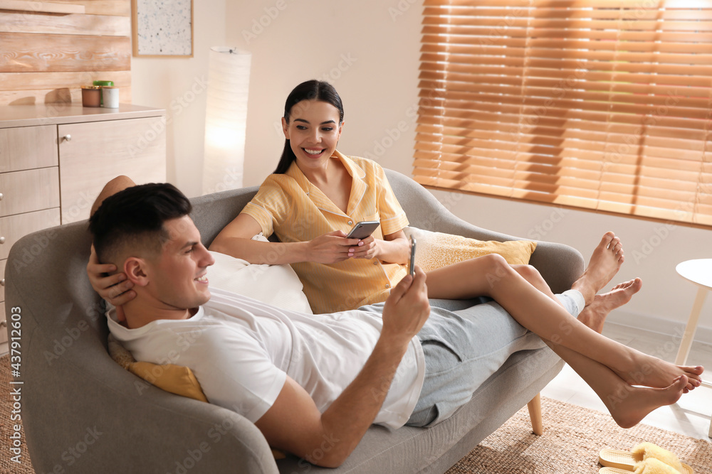 Leinwandbild Motiv - New Africa : Happy couple in pyjamas with gadgets spending time together on sofa at home