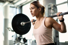 Determined Female Athlete Having Weight Training In A Gym.