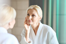 Gorgeous Mid Age Adult 50 Years Old Blonde Woman Standing In Bathroom After Shower Touching Face, Looking At Reflection In Mirror Doing Morning Beauty Routine. Older Dry Skin Care Concept.