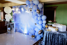 Blue Photo Zone With Balloons, Banner And Macarons On Birthday Party