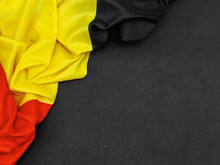 Belgian Flag On Black. Belgian Flag Lies On The Left On A Black Background With Space For Text To The Right, Top View Close-up.
