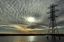 High Voltage Tower On A Lake Under Gray Clouds