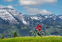 Smiling Senior Woman Riding Her Electric Mountain Bike On A Sunny Day In Early Spring With Yello Flowers On The Meadows Below The Snow Capped Mountains Of Nagelfluh Chain Near Oberstaufen, Allgaeu