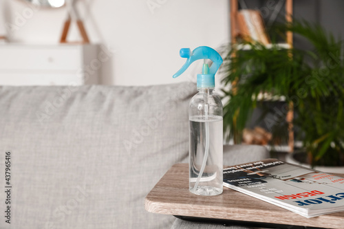 Bottle of air freshener and magazine on table in living room