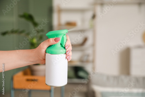 Young woman with air freshener at home, closeup