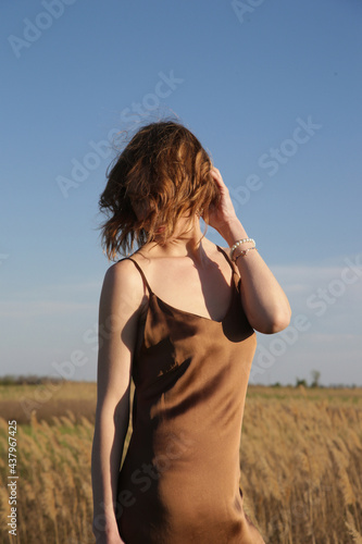 Obraz na plátně Portrait of beautiful woman in silk camisole dress on windy summer day