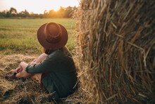 Stylish Woman In Hat Looking At Sunset Light, Sitting At Haystacks In Summer Field. Atmospheric Tranquil Moment In Countryside. Young Female Enjoying Evening At Hay Bale In Warm Sunshine