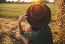 Stylish Woman In Hat With Straw Looking At Sunset Light, Sitting At Haystacks In Summer Field. Atmospheric Tranquil Moment In Countryside. Young Female Enjoying Evening At Hay Bale In Warm Sunshine