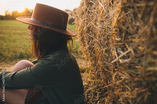 Beautiful stylish woman in hat sitting at haystacks in evening sunset in summer field Fototapet