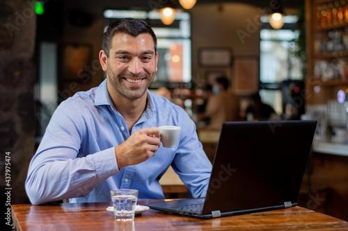 Obraz na plátně Hombre bebiendo cafe con su laptop en un descanso del trabajos sentado en una me