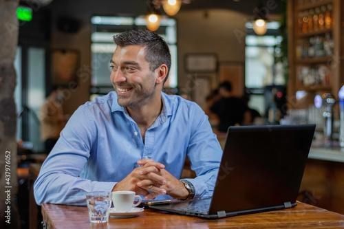 Fototapeta joven chico mirando hacia afuera mientras toma un descanso de su trabajo bebiend