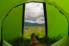 Dramatic View From Inside The Tent During A Cloudy Day, Spring Landscape In A Campground With Flowers In The Foreground And Green Hills With Forests That Reach The Top Of The Mountain In The Distance.