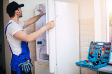 Professional Young Repairman In Worker Uniform And Cap With Modern Toolbox With Equipment Is Repairing Of Refrigerator On The Kitchen