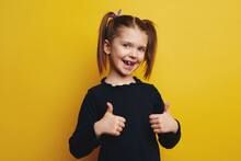 Little Girl With Opened Mouth Showing Thumbs Up Isolated On Yellow Wall
