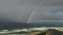 River Mouth Leading Out To A Popular Surfing Beach With A Dazzling Rainbow And Rain Clouds Above A Turbulent Ocean Swell