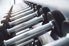 Gym And Workout Concept With Rack Of Black And Metal Dumbbells In Sport Fitness Center. 3D Rendering.