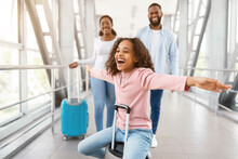 Happy Black Family Traveling With Daughter, Having Fun In Airport