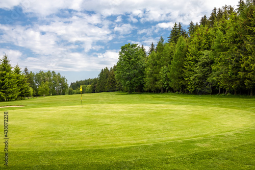 Golf green with flag in spring nature under blue sky #438072230