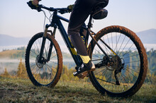 Horizontal Cropped Snapshot Of Biker's Legs, Sitting On Bicycle. Close-up View On Bike, Wheels In Mud, After Morning Ride On Mountains Trails. Athlete Enjoying The Moment Of Sunrise